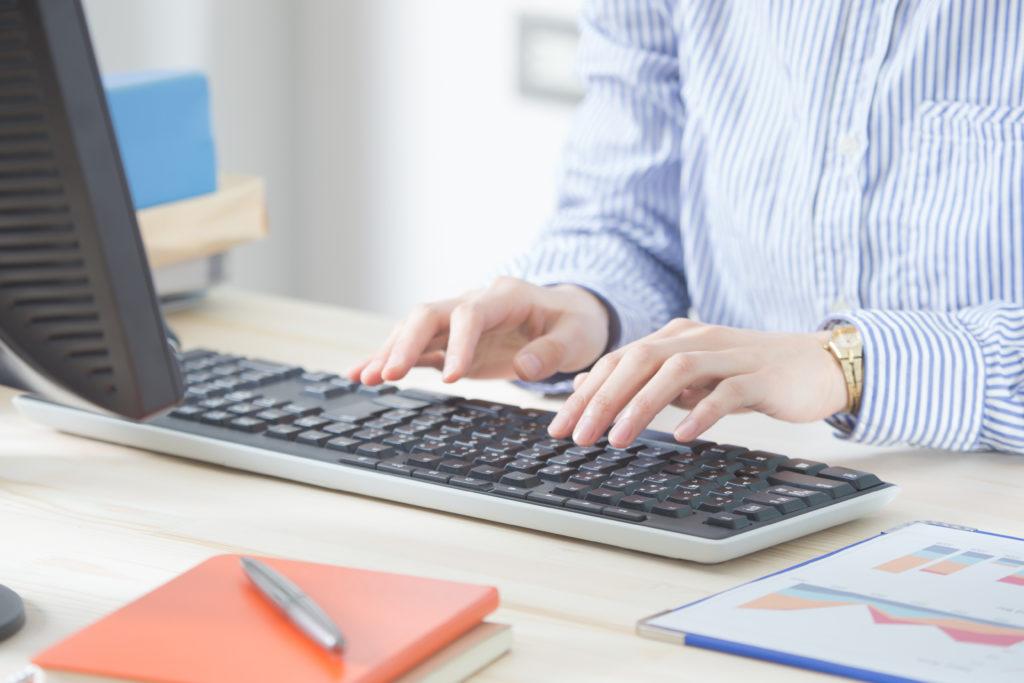 close up of computer keyboard with person's hands typing