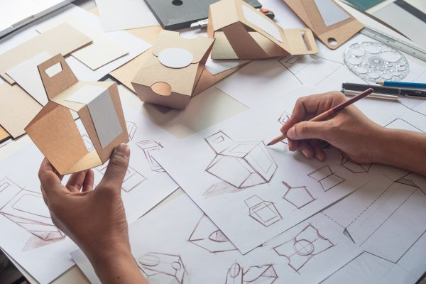 Product designer draws a concept for a new box while holding a working model of the box