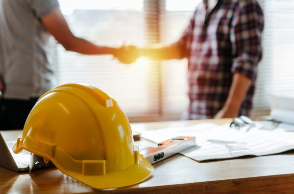 yellow safety helmet on workplace desk with construction worker team hands shaking greeting start up plan new project contract in office center at construction site, partnership and contractor concept