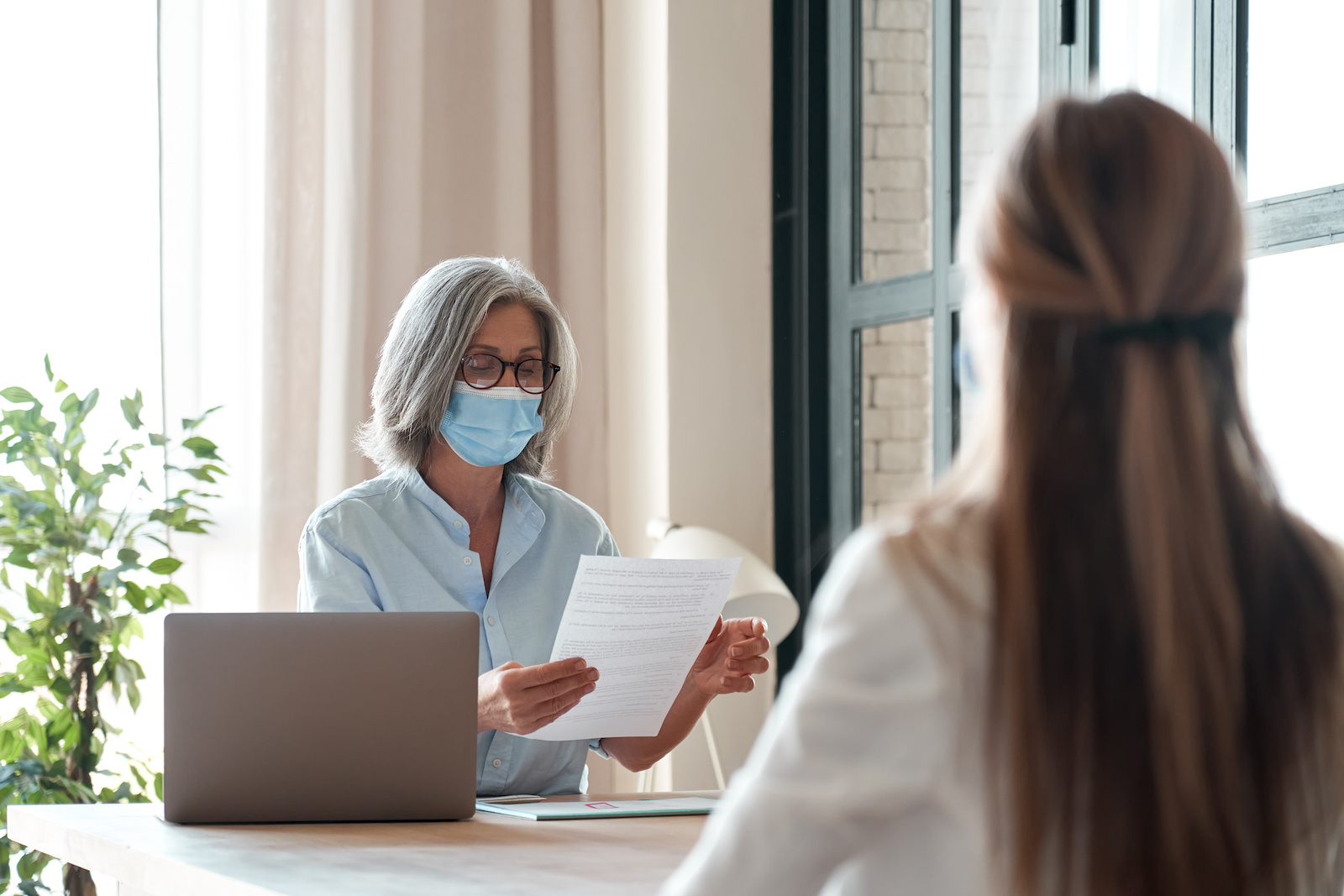hr manager checking female job applicant cv resume at job interview meeting. Senior employer wearing face mask reading seeker employment application. Social distance and safety at work concept.